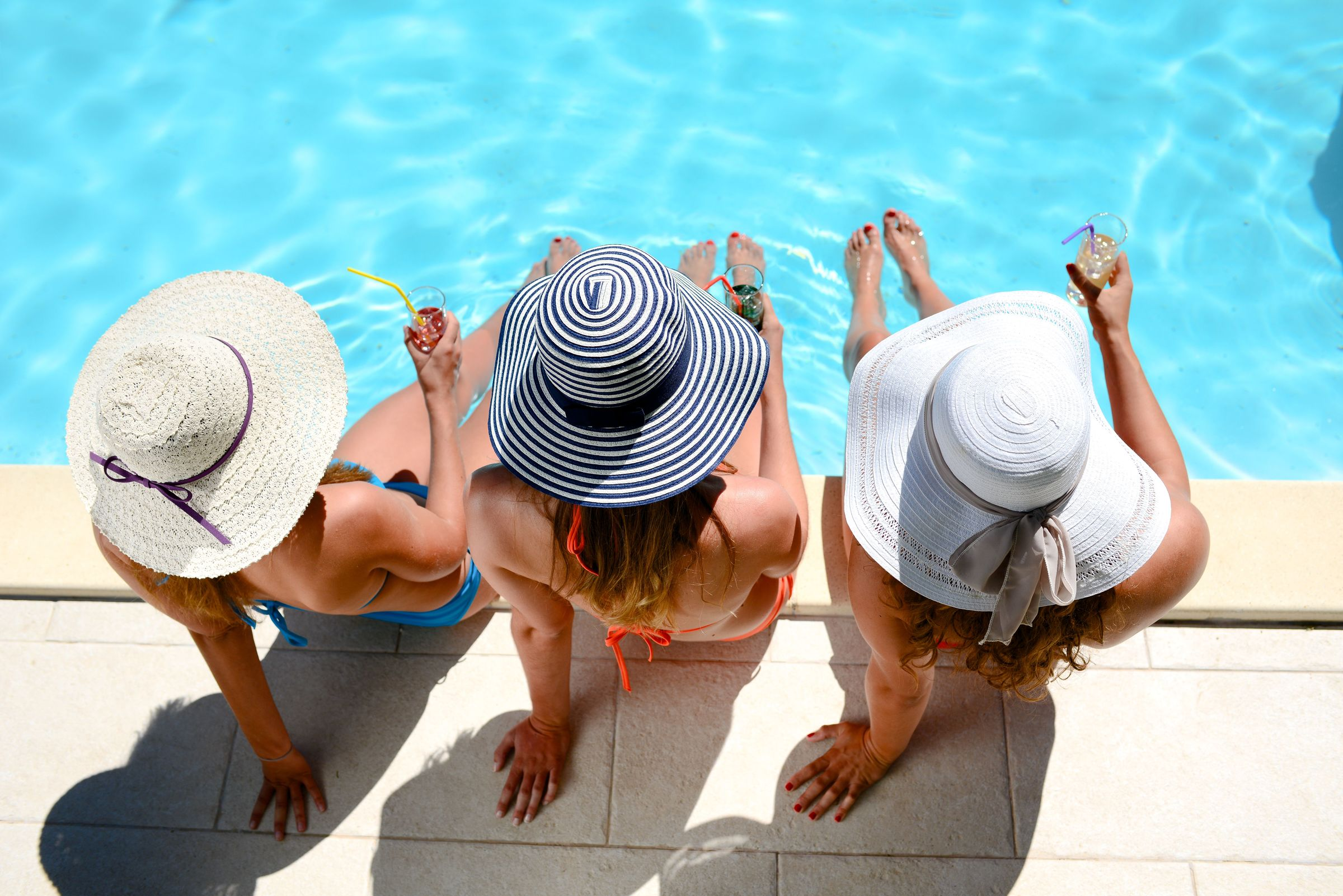 3 women sitting on the edge of a pool