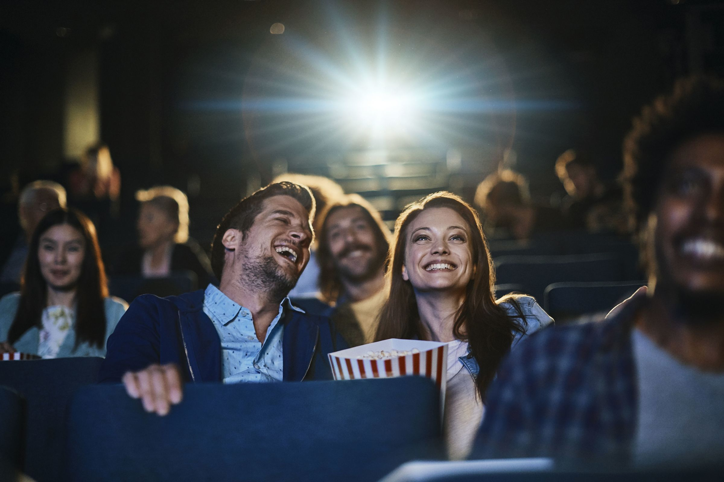 man and woman laughing in a movie theatre