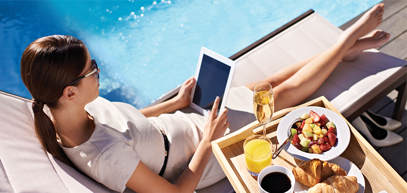 woman lounging by a pool with an iPad and food tray