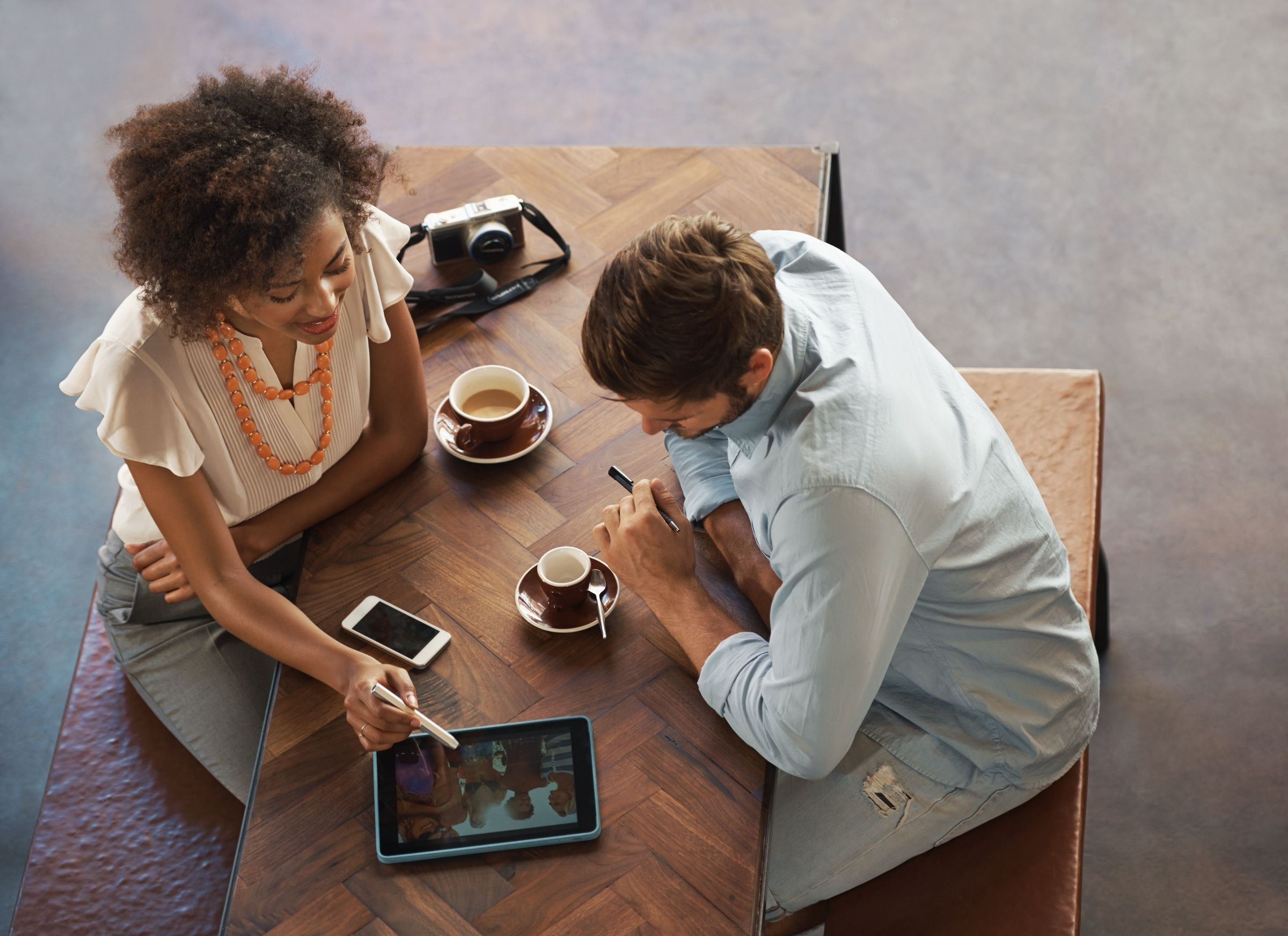 man and woman sitting at a table looking at an iPad