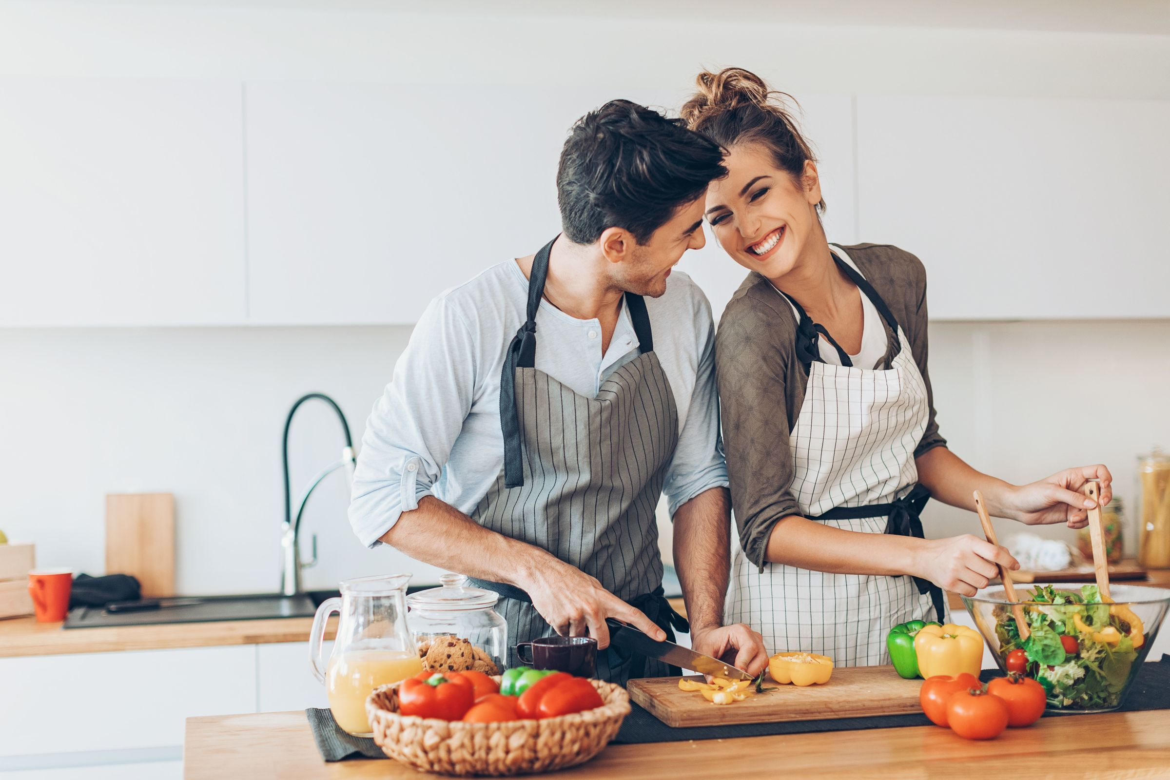 happy, smiling couple cooking