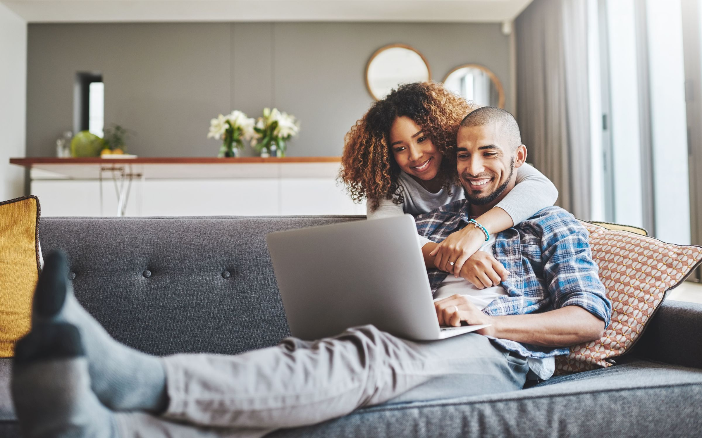 man and woman smiling and looking at a laptop screen